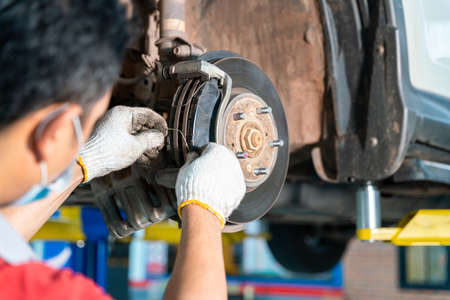 Car mechanic hands replace brakes in garage. Mechanic technician worker installing car wheel at maintenance. Worker changing brake disc in auto repair service center Stock Photo