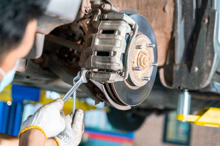 Car mechanic checking a disc brake of the vehicle for repair, in process of new tire replacement. Car brake repairing in garage at auto repair service center Stock Photo