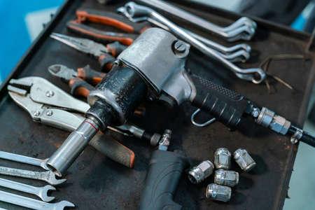 equipment of car mechanic adjusting tension in vehicle suspension Element at auto repair service center, car suspension concept
