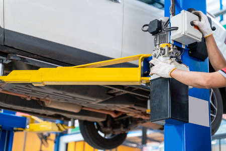 hand of auto mechanic using a car lift in car repair service centre background Stock Photo