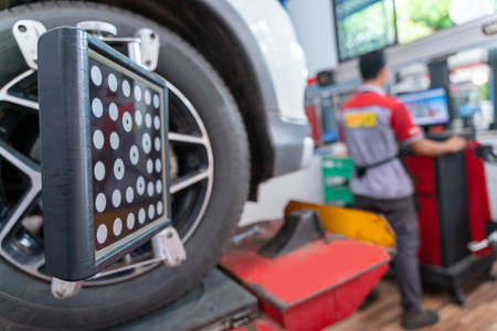 Car wheel balancer calibrate with laser reflector attach on each tire to center driving adjust. Balancing tire wheel machine at car repair service center. Stock Photo