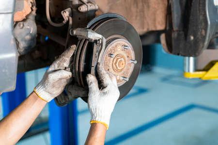 car mechanic repairs breakes from vehicle in auto repair service center Stock Photo