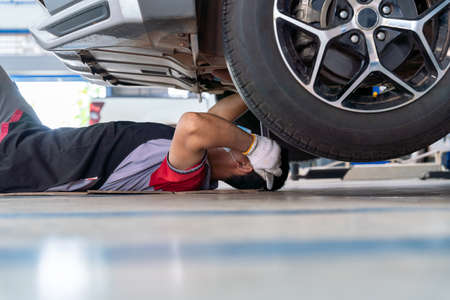 car mechanic adjusting tension in vehicle suspension Element at auto repair service center, car suspension concept Stock Photo