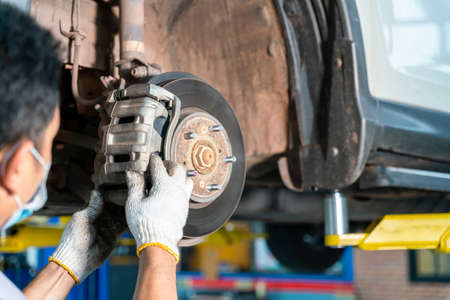 car mechanic examining car wheel brake disc and shoes of lifted automobile at auto repair service center