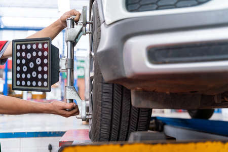 auto mechanic install car wheel balancer calibrate with laser reflector attach on each tire to center driving adjust. Balancing tire wheel machine at car repair service center.