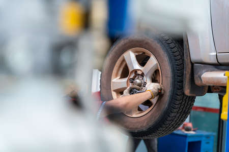 hands of mechanic with tool, changing tyre of car at auto repair service center