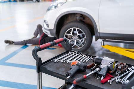 select focus equipment of car mechanic adjusting tension in vehicle suspension Element at auto repair service center, car suspension concept Stock Photo