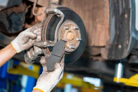 Car mechanic repairing brakes on car in auto repair service center Stock Photo