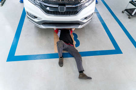 Top view of mechanic in uniform lying down and working under car, car mechanic adjusting tension in vehicle suspension Element at auto repair service center, car suspension concept