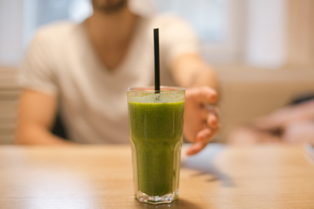 A handsome boy wants to take a green smoothie with his hand from the table Stock Photo