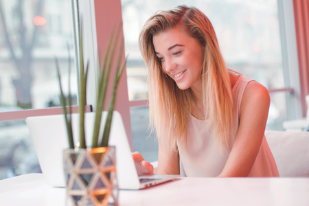 elegant young positive beautiful girl,sitting using laptop computer in a cafe,successful happy business woman,working,looking for information,browsing internet, smiling and looking at you,blurred background Reklamní fotografie