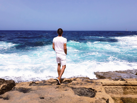 handsome young man in white standing on the edge of rock looking at sea waves, blue sky,calm down, outdoor sexy fashion model,believe in hope,traveling tourist,feel freedom,independence