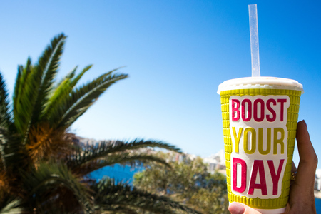 bright big plastic glass with words boost your day on the blue sky background and palm trees,a hot summer day,drink smoothie
