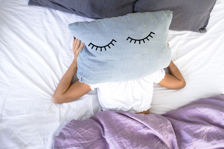 a young girl sleeping in white bed doesn't want to get up early in the morning,covering her face with a pillow with closed eyes on it. Stock Photo
