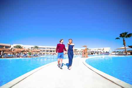 a beautiful young couple in love walking past swimming pool under bright blue sky,traveling  having holiday in a hotel in Egypt ,relaxing and enjoying sun Stock Photo