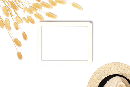 Top view of white frame mockup with decorative dried grass and hat on white background in vintage style.