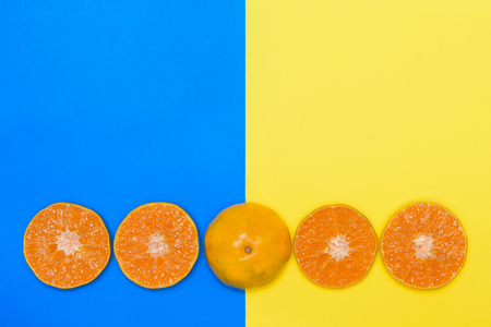 Orange fruit half cut on blue and yellow backgrounds. Top view flat lay style with copy space.