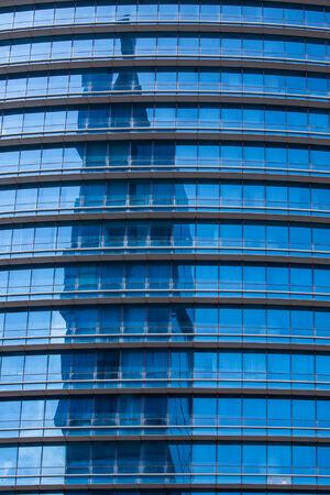 Reflextion on modern blue glass of office windows, Jakata photo