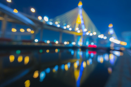 Out of focus bokeh lights of Phomipoon Bridge with water reflextion, Bangkok Thailand photo