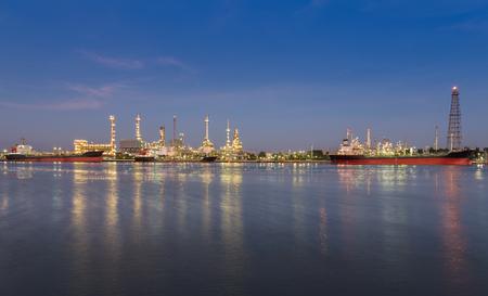 reflexion: Panorama de la refiner�a de petr�leo en el crep�sculo, junto con la reflexi�n r�o Foto de archivo