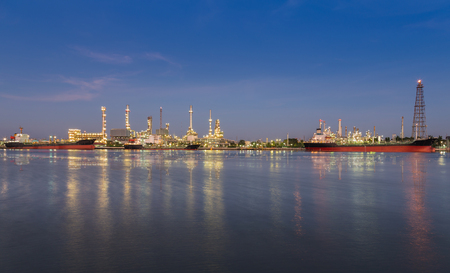 reflexion: Panorama of Oil refinery at twilight along with river reflexion