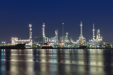 Oil refinery at twilight with river reflexion photo