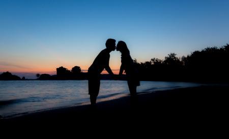 Silhouet van minnaars zoenen op het strand bij Schemering