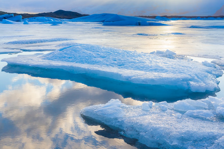 reflexion: Blue icebergs floating in Jokulsarlon lagoon Iceland with sky reflexion