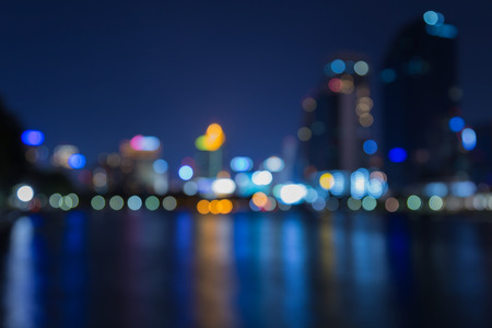 City night lights out of focus with water reflection, twilight Archivio Fotografico