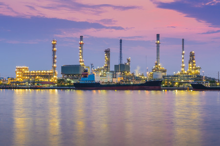 Oil refinery industry plant during twilight morning along with water reflection photo