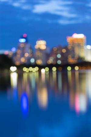 reflection water: City skyline bokeh lights during twilight with water reflection