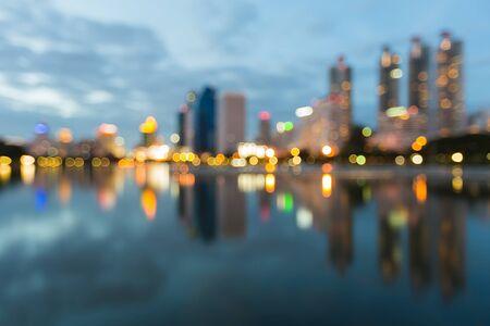 Abstracte stad bokeh lichten tijdens blauwe uren, met water reflectie