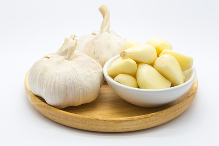 Fresh garlic on wooden plate on white background