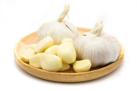 Garlic on wooden plate on white background