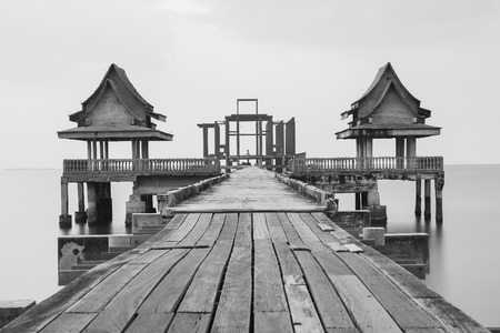 Black and white, wooden bridge leading to unfinished temple building in the sea Standard-Bild