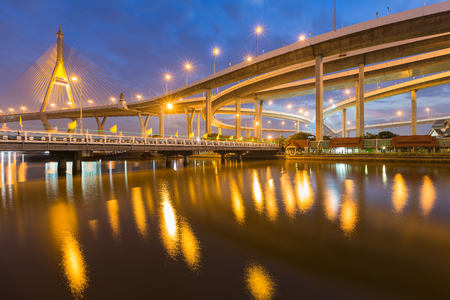 night highway: Suspension bridge and highway curved riverside with twilight scene