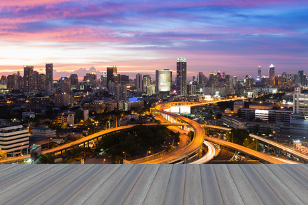interchanged: Opening wooden floor, Beautiful skyline of Bangkok City downtown and road interchanged after sunset Stock Photo