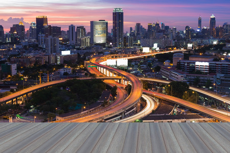 interchanged: Opeing wooden floor, Aerial view city road interchanged with city background skyline night view Stock Photo
