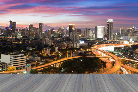 interchanged: Open wooden floor, city road interchanged and downtown background with beautiful sky after sunset