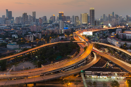 highway traffic: Aerial view city downtown background with highway intersection during twilight Stock Photo