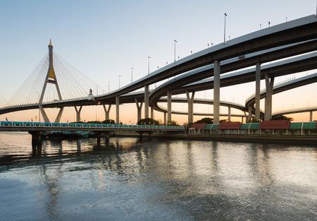 interchanged: Curve of suspension bridge and hight way interchanged at riverside in twilight, Bangkok Thailand Stock Photo