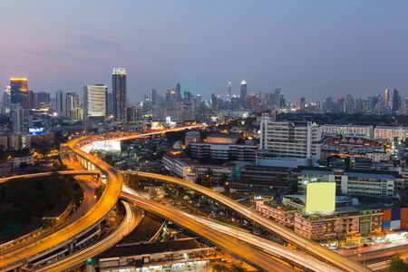 interchanged: Bangkok highway interchanged with city downtown background during twilight Stock Photo