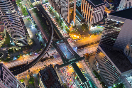interchanged: Aerial Bangkok city downtown road interchanged and sky train station, night view