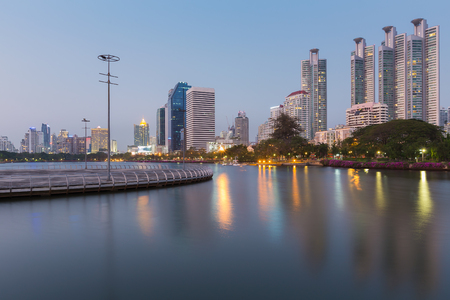 benjakitti: City office building with water reflection in public park during twilight