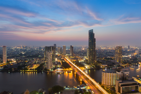 plano: Beautiful sky after sunset, aerial view over city downtown and Bangkok main river, long exposure, Thailand