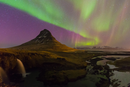 auroral: Northern lights moving over Kirkjufell volcano with fully of stars in sky, Iceland natural landscape