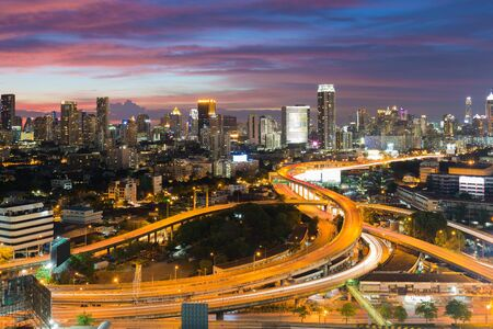 interchanged: Aerial view highway interchanged with city downtown background at twilight, long exprosure Stock Photo