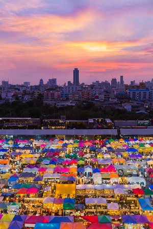 Aerial view, multiple colours weekend market roof top with dramatic sky background after sunset