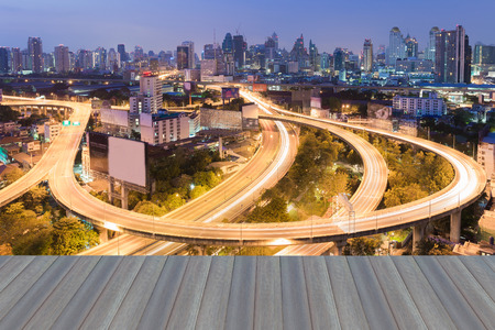 interchanged: Opening wooden floor, Curved highway interchanged with city downtown background at twilight Stock Photo