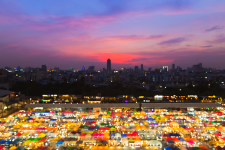 fleamarket: Abstract blurred bokeh lights aerial view night market roof top, multiple colours background